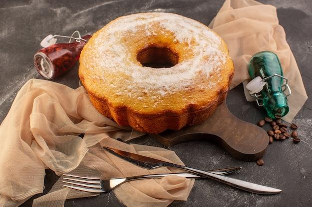 Eine vorderansicht gebackenen runden kuchen mit zuckerpulver und kaffeesamen auf dem holzschreibtisch Kostenlose Fotos