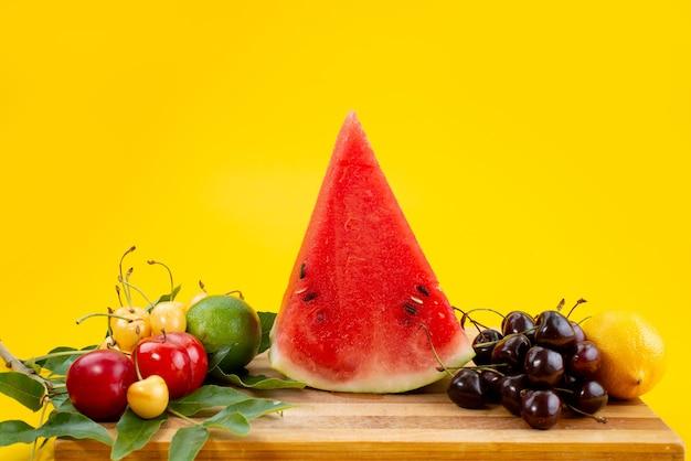 Eine vorderansicht geschnittene frische wassermelone alogn mit frischen früchten auf gelbem schreibtisch Kostenlose Fotos