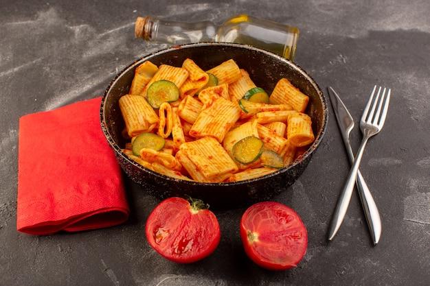Eine vorderansicht kochte italienische nudeln mit tomatensauce und gurke in der pfanne auf der dunklen oberfläche Kostenlose Fotos