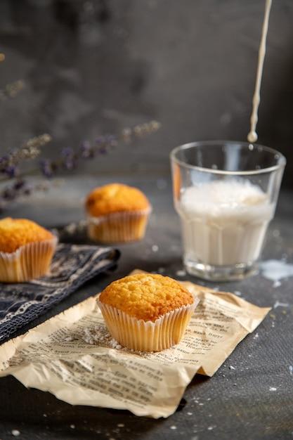 Eine vorderansicht köstliche kleine kuchen mit lila blumen und milch auf dem grauen tischplätzchen-teekeks süß Kostenlose Fotos