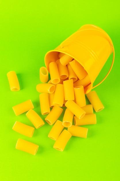 Eine vorderansicht-nudeln innerhalb des korbs bildeten rohen inneren gelben korb auf dem grünen hintergrundmahlzeitnahrungsmittel-italienischen spaghetti Kostenlose Fotos