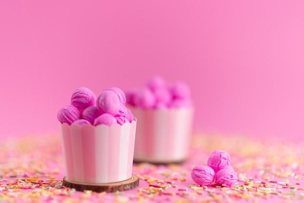 Eine vorderansicht rosa, kekse köstlich und lecker zusammen mit bunten süßigkeiten auf rosa, kekskekszucker Kostenlose Fotos
