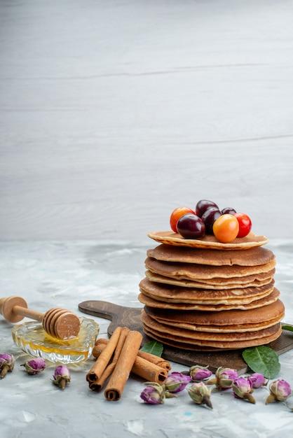 Eine vorderansicht runde pfannkuchen gebacken und lecker mit kirschen auf dem hellen schreibtisch kuchen obst Kostenlose Fotos