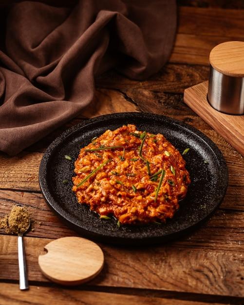Eine vorderansicht tomate saugte fleisch gebraten und heiß in schwarzer platte auf dem holztisch essen mahlzeit fleisch Kostenlose Fotos