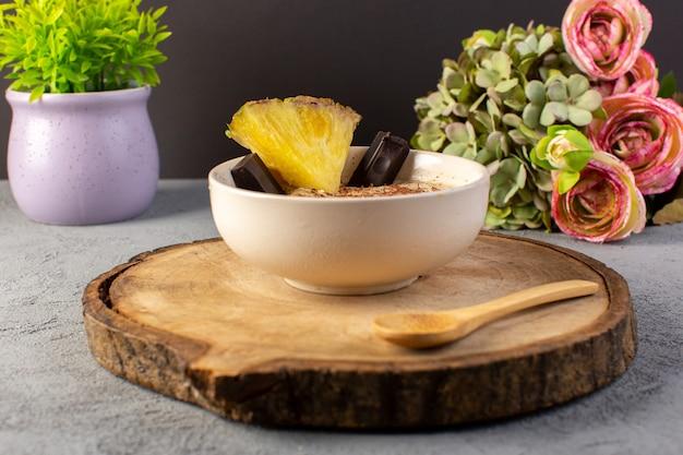 Eine vordere geschlossene ansicht choco dessert braun mit ananasscheibe choco bars blumen auf dem braunen holzschreibtisch und grau Kostenlose Fotos