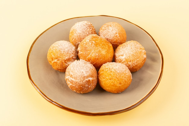 Eine vordere geschlossene ansicht zuckerpulverkuchen um süße gebackene köstliche kleine kuchen innerhalb der runden plattform Kostenlose Fotos