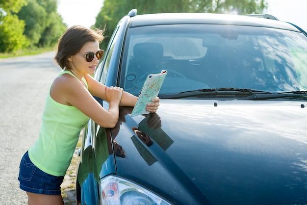 Eine weibliche fahrerlesekarte nahe auto Premium Fotos