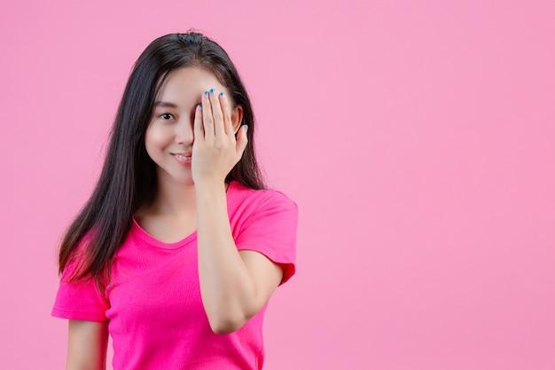 Eine weiße asiatische frau legt ihre linke hand auf ihre augen auf ein rosa. Kostenlose Fotos
