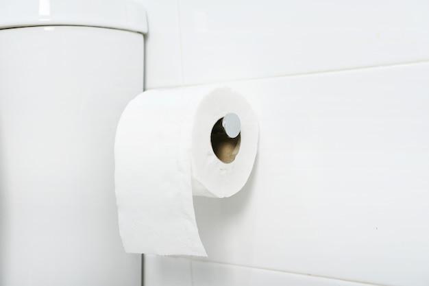 Eine weiße rolle aus weichem toilettenpapier, die ordentlich am chromhalter an einer weißen badezimmerwand hängt. nahansicht Premium Fotos