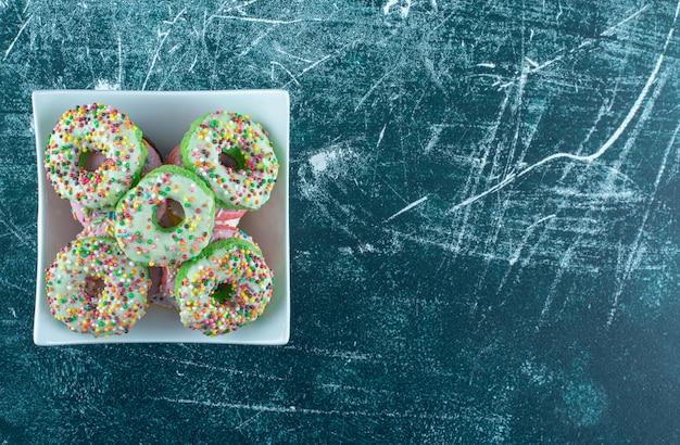 Eine weiße schüssel voll von süßen donuts auf einem blauen hintergrund. hochwertiges foto Kostenlose Fotos