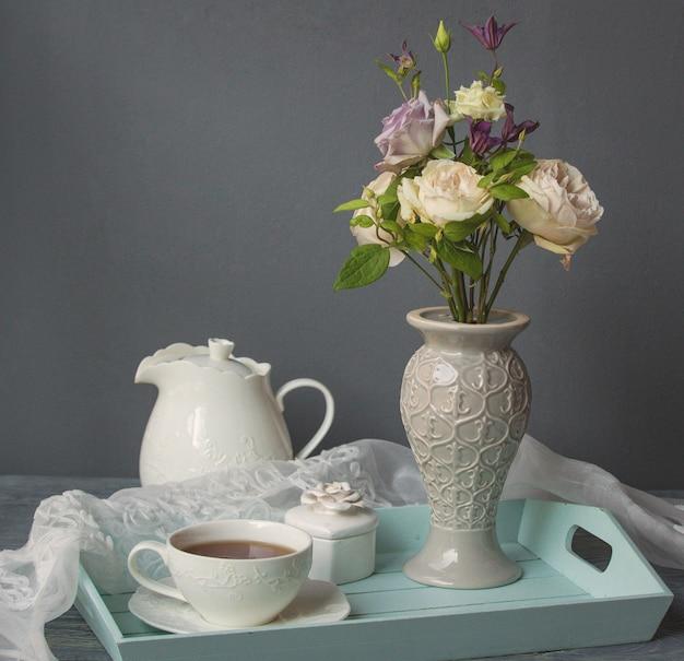 Eine weiße tasse kaffee, wasserkocher und blumenvase Kostenlose Fotos