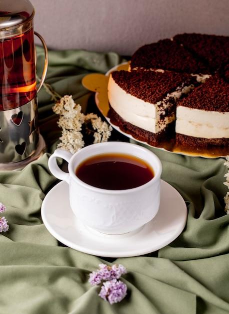 Eine weiße tasse tee und ein kessel mit schokolade oreo kuchen. Kostenlose Fotos