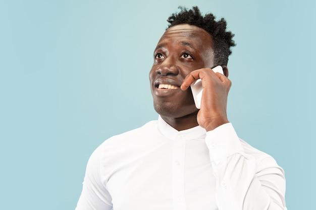 Einen anruf tätigen. junger afroamerikaner mit smartphone. Kostenlose Fotos