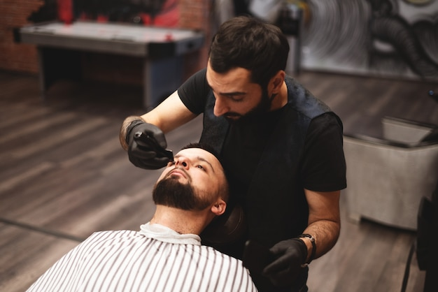 Einen bart im friseursalon mit einem gefährlichen rasiermesser rasieren. friseur bartpflege. trocknen, schneiden, bart schneiden. Premium Fotos