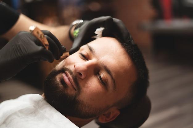Einen bart in einem friseursalon mit einem gefährlichen rasiermesser rasieren. Premium Fotos