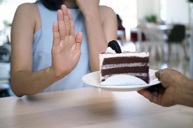 Eines der mädchen im gesundheitswesen schob mit der hand einen teller schokoladenkuchen hinein. Premium Fotos