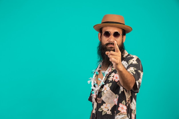 Eines glücklichen mannes mit einem langen bart, der einen hut trägt und ein gestreiftes hemd trägt, das eine geste auf einem blau zeigt. Kostenlose Fotos