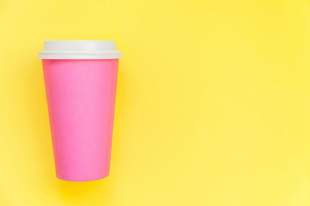 Einfach flach legen sie die designrosapapierkaffeetasse, die auf gelbem buntem modischem hintergrund lokalisiert wird Premium Fotos