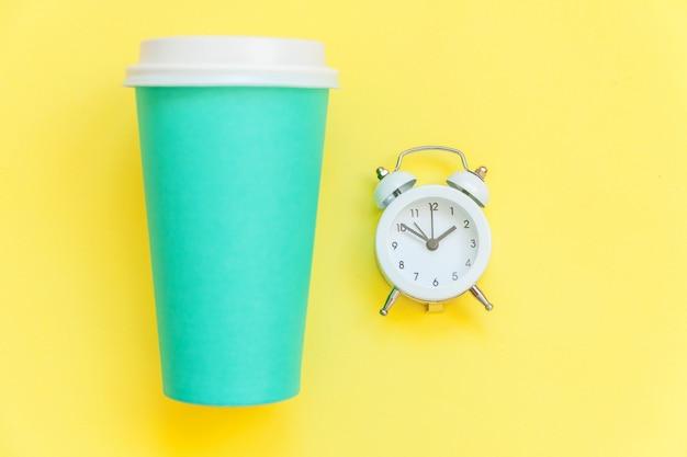Einfach flach legen sie die kaffeetasse und wecker des blauen papiers des designs, die auf gelbem buntem modischem lokalisiert werden Premium Fotos