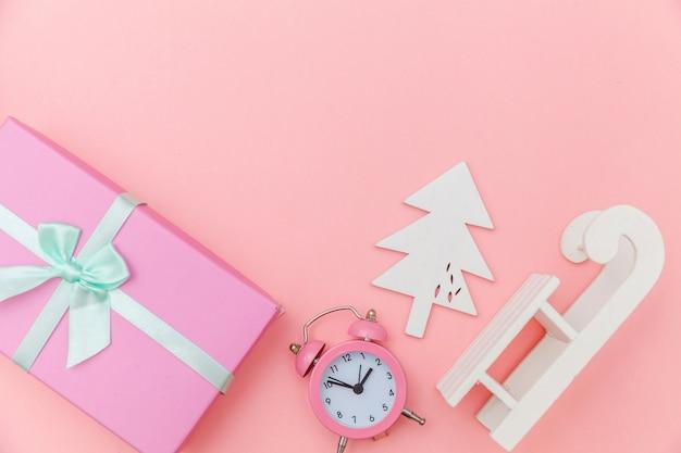 Einfach minimaler zusammensetzungswinter wendet verzierungsschlitten-tannenbaumball-geschenkbox lokalisierten rosa pastellhintergrund ein Premium Fotos
