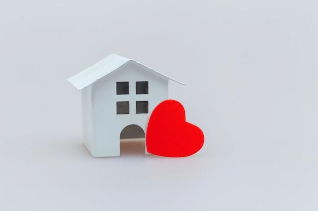 Einfach minimales design mit weißem spielzeugminiaturhaus mit dem roten herzen lokalisiert auf weiß Premium Fotos
