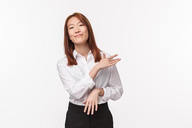 Einfach. sorgloser und ungestörter asiatischer profi, die schultern mit erfreutem, entspanntem ausdruck abbürsten, projekt als keine große sache abschließen, leicht erfolg erzielen, Premium Fotos