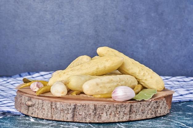 Eingelegte gurken, knoblauch, paprika und blatt auf holzteller mit tischdecke. Kostenlose Fotos