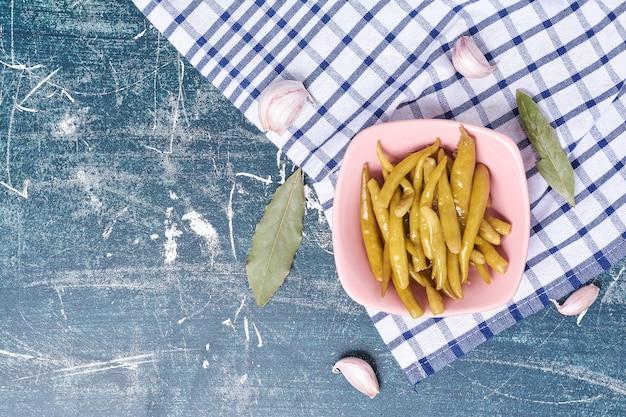 Eingelegte peperoni auf teller mit blatt, knoblauch und tischdecke. Kostenlose Fotos