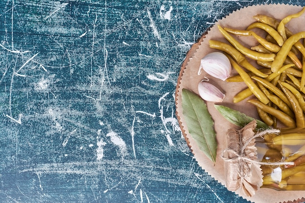 Eingelegte peperoni im glas und auf teller mit blatt und knoblauch. Kostenlose Fotos