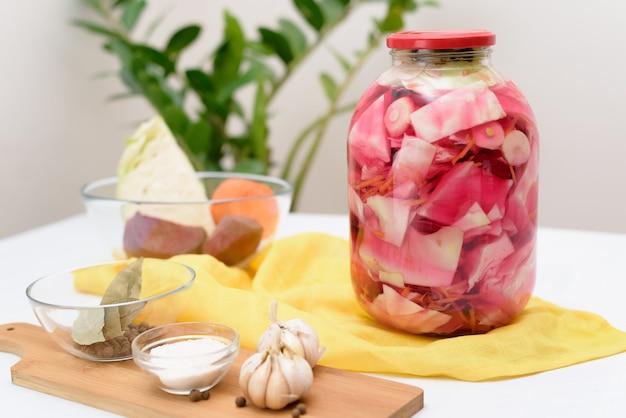 Eingelegter rosakohl fermentativ mit rüben und karotten in salzlake in einem glas auf hellem hintergrund. Premium Fotos