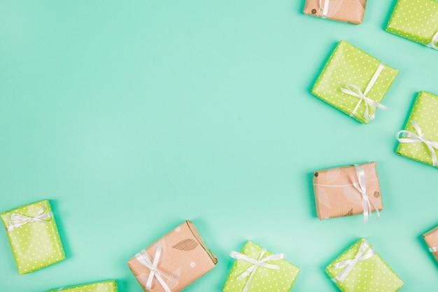 Eingewickelte Geschenke gebunden mit weißem Bandbogen auf grünem Hintergrund Kostenlose Fotos