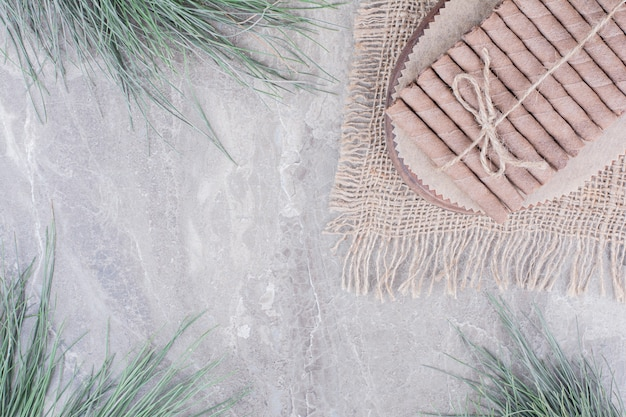 Eingewickelte waffelstangen auf einem rustikalen brett Kostenlose Fotos
