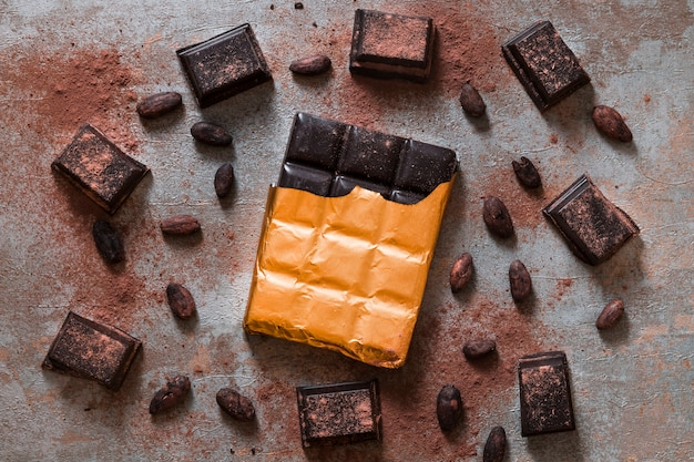 Eingewickelter schokoriegel und kakaobohnen auf rustikalem hintergrund Kostenlose Fotos
