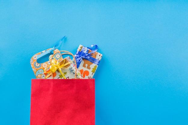 Eingewickeltes geschenk in der roten einkaufstasche über normalem hintergrund Kostenlose Fotos