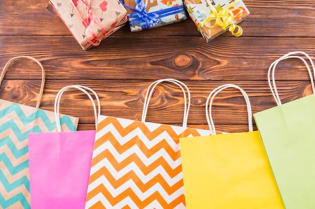 Eingewickeltes geschenk und dekorative papiereinkaufstasche über holzoberfläche Kostenlose Fotos