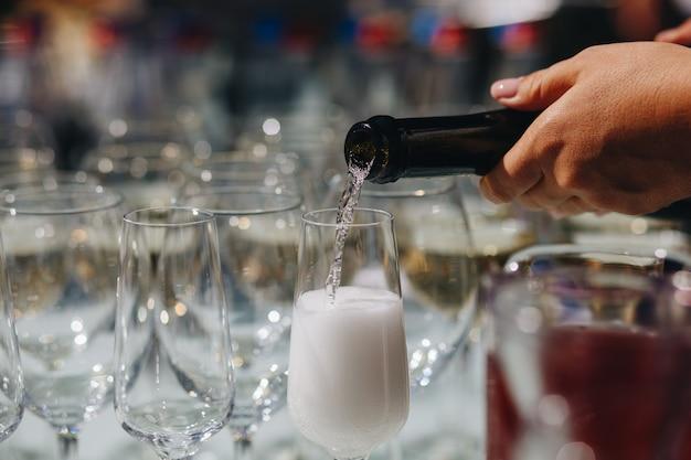 Eingießender champagner des kellners in den gläsern in einer verpflegung Premium Fotos