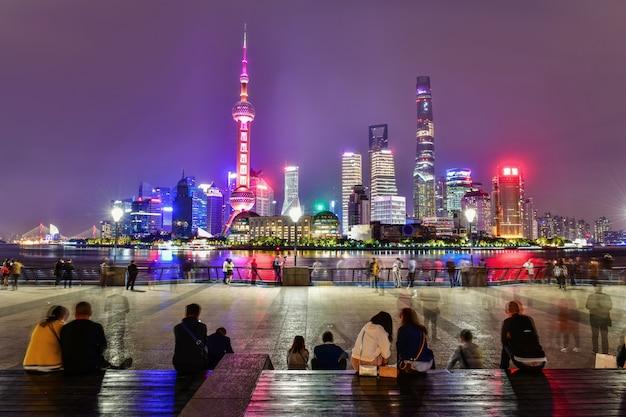 Einheimische und touristen, die am huangpu-flussufer die promenade in shanghai, china sich entspannen und besichtigen Premium Fotos