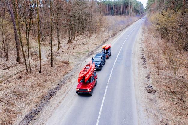 Einige autos mit kajaks auf dem dachgepäckträger, der auf die straße unter bäumen fährt Kostenlose Fotos