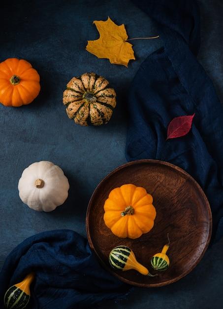 Einige dekorative kürbisse auf braunem holzteller und dunklem tisch mit serviette Premium Fotos