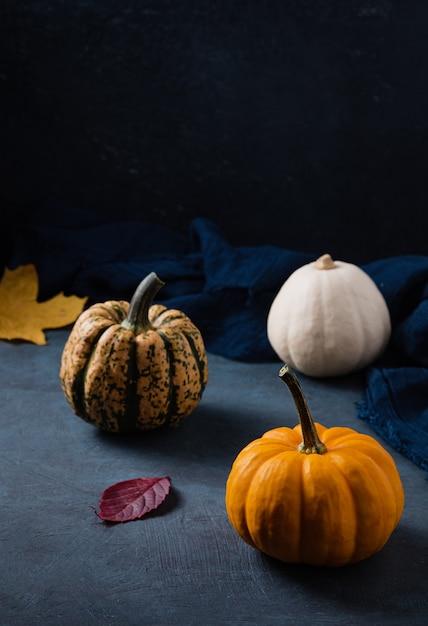 Einige dekorative kürbisse und herbstblätter auf dunklem tisch mit serviette Premium Fotos