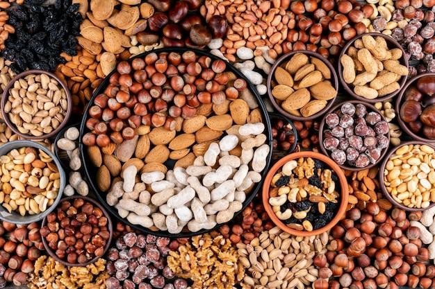Einige der verschiedenen nüsse und getrockneten früchte mit pekannuss, pistazien, mandeln, erdnüssen, cashewnüssen, pinienkernen in verschiedenen schalen und schwarzer pfanne flach liegen. Kostenlose Fotos