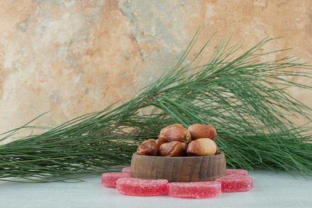 Einige der zuckerroten marmelade mit der holzschale voll von getrockneten früchten auf weißem hintergrund. hochwertiges foto Kostenlose Fotos