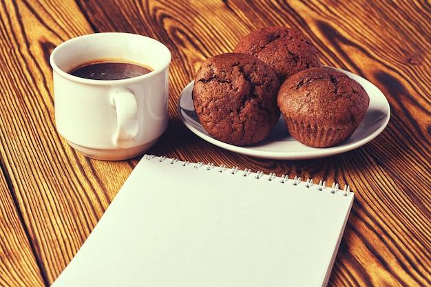 Einige dunkle schokoladenteigmuffins mit einem tasse kaffee und einem notizblock auf einem holztisch. Premium Fotos
