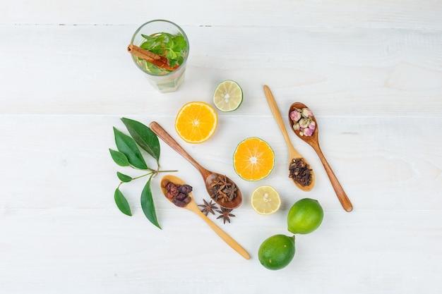 Einige fermentierte getränke mit zitrusfrüchten, nelken und getrockneten früchten auf weißer oberfläche Kostenlose Fotos