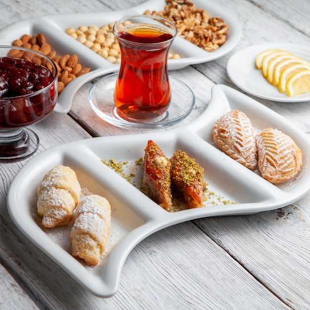 Einige köstliche desserts mit tee, nüssen, fruchtmarmelade, geschnittener zitrone auf weißem hölzernem hintergrund, hohe winkelansicht. Kostenlose Fotos