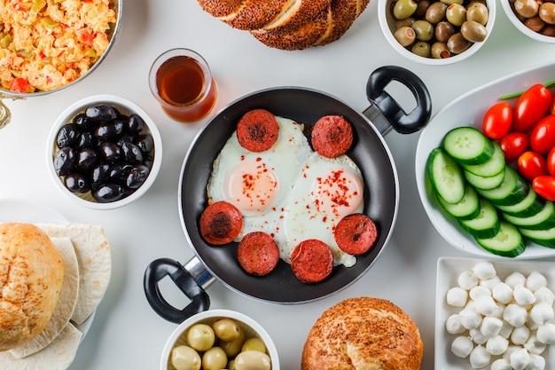 Einige köstliche mahlzeiten mit salat, gurken, türkischem bagel, einer tasse tee in einer pfanne und einer kanne auf weißer oberfläche, draufsicht Kostenlose Fotos