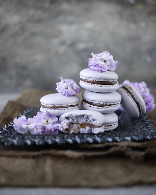 Einige lavendel macarons auf grauem hintergrund, dekoriert mit blumen. französisches gebäck Premium Fotos