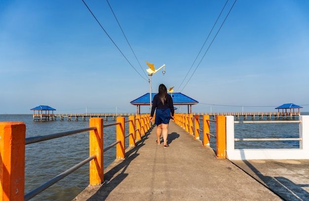 Einige leute, die auf die brücke im blauen meer gehen Premium Fotos