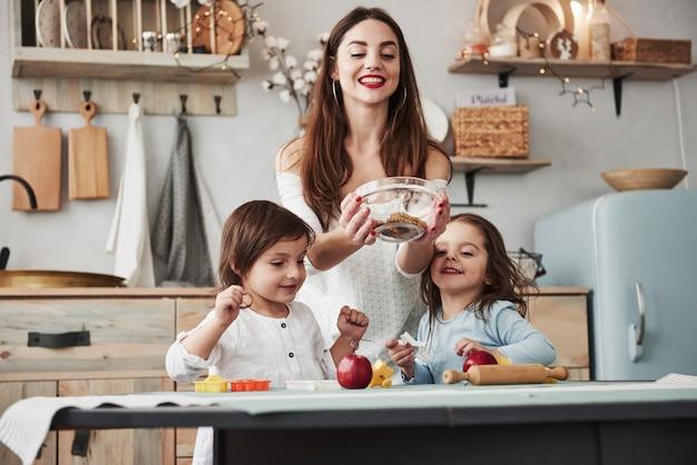 Einige süßigkeiten stören nicht. junge schöne frau geben die plätzchen, während sie nahe der tabelle mit spielwaren sitzen Premium Fotos