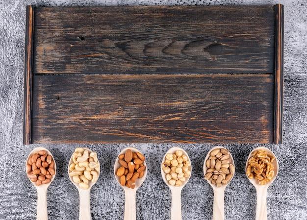 Einige von verschiedenen nüssen und getrockneten früchten mit pekannuss, pistazien, mandel, erdnuss, in einem holzlöffel auf holzschneidebrett Kostenlose Fotos